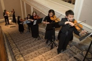 Preparatory Strings students perform for guests on the Four Season's Grant Staircase