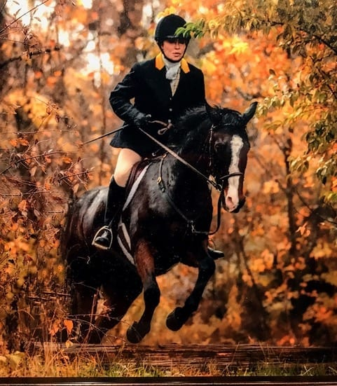 Female riding a black horse