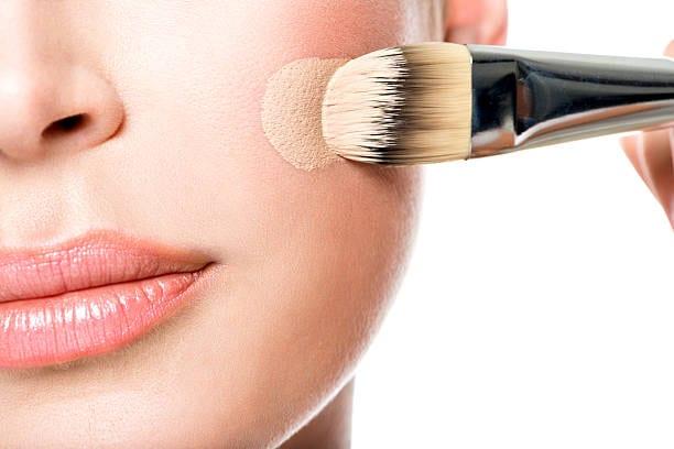 Makeup artist applying liquid tonal foundation on the face of the woman. Closeup photo of cheek