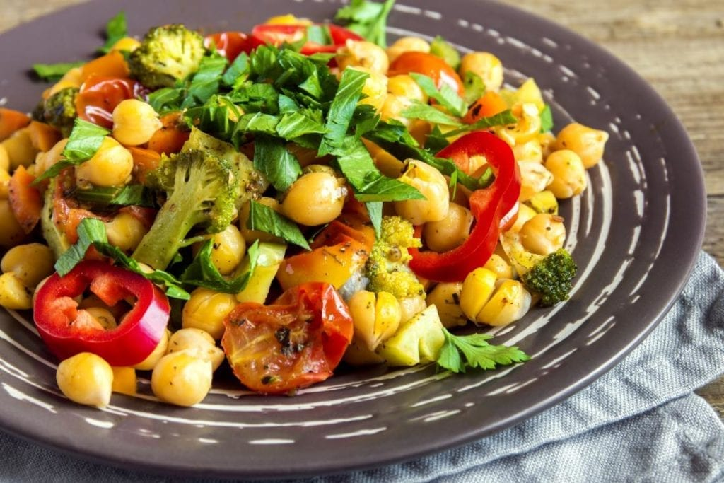 vegan stew with chickpeas and vegetables, including tomatoes, broccoli, and peppers