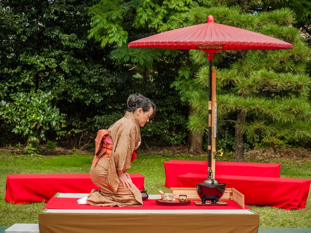 Tea being prepared outdoors, the hostess wears a brown kimono